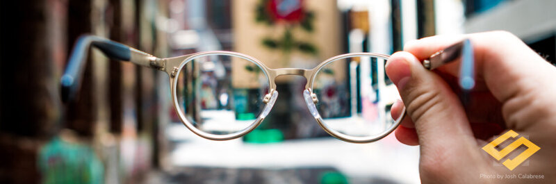 glasses held up to a city street