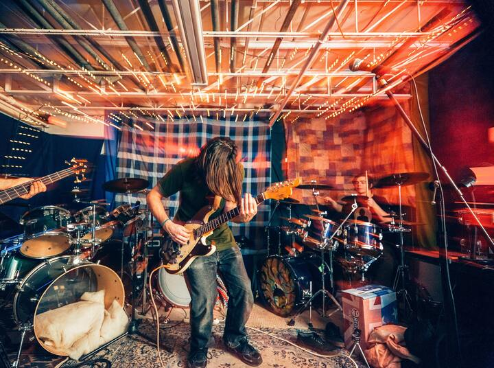 photo of a rock band playing in a rehearsal space